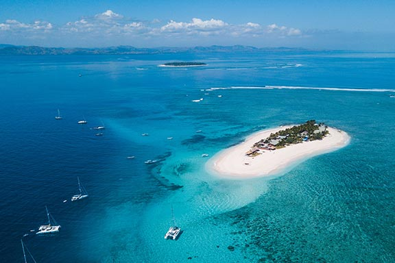 aerial-image-of-namotu-island-surrounded-by-boats-and-reef-with-beautiful-water