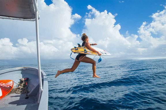 girl-jumping-into-water-off-boat-for-surfing-break-near-namotu-island