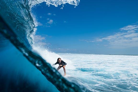 girl-riding-big-wave-at-wilkes-passage-namotu-island-fiji