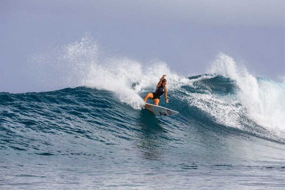 girl-surfing-wave-near-namotu-island-fiji