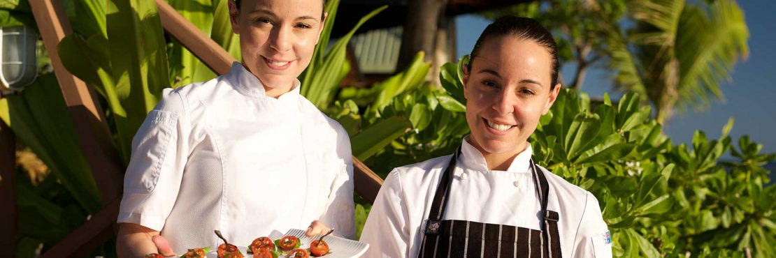 monica-and-jacinta-smiling-chefs-on-namotu-island-with-food-banner