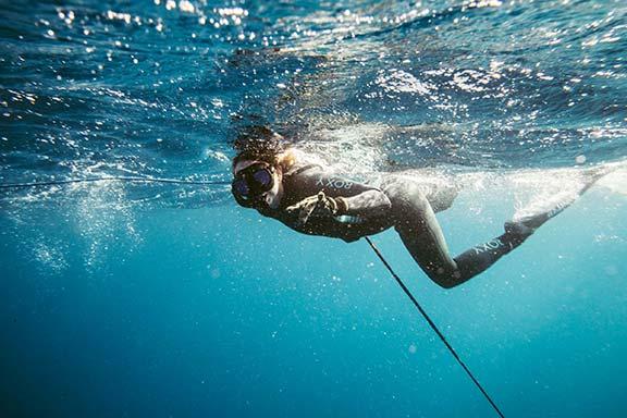 woman-diving-in-blue-water-off-namotu-island-fiji